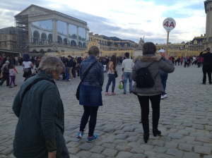 Our interpretive guide leads our group with her lollipop toward the golden gates of Versailles.